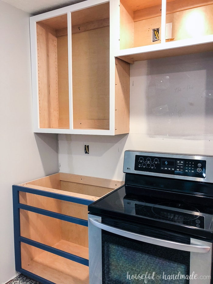 Kitchen with cabinets installed without cabinet doors yet. Base cabinet is a drawer base and uppers are over stove.