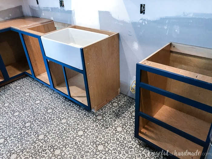 Navy blue base cabinets and a patterned vinyl floor make a huge statement in a farmhouse kitchen. See our tips for serving a kitchen remodel at Housefulofhandnmade.com.