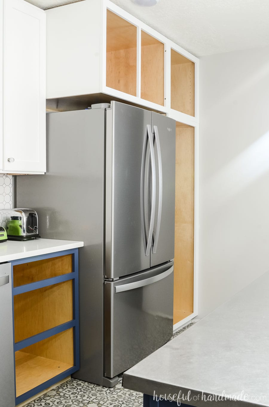 Stainless steel refrigerator surrounded by deep white cabinets for a pantry. Budget farmhouse kitchen reveal at Housefulofhandmade.com