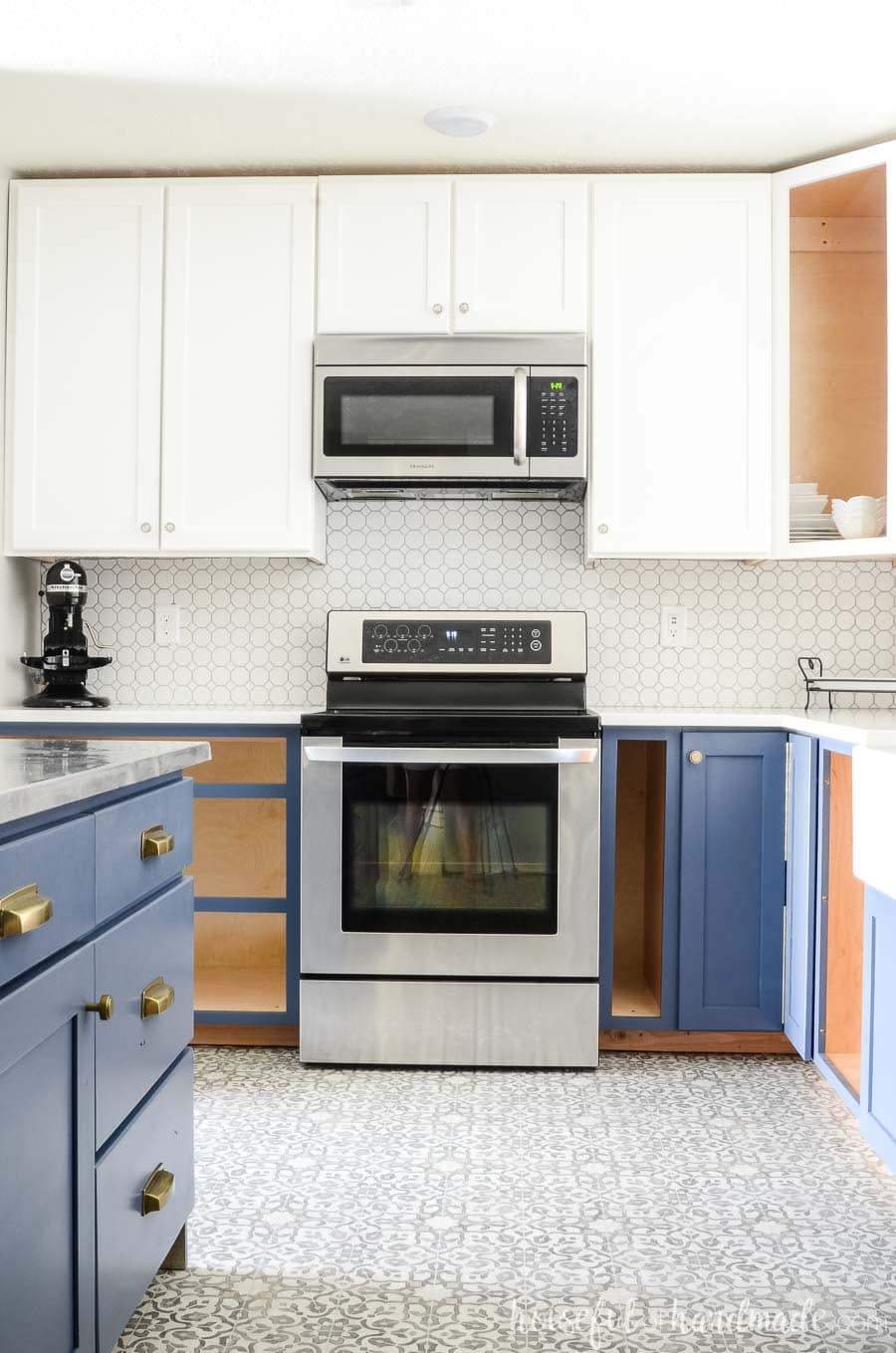 A complete kitchen remodel on a budget is possible. We turned our outdated kitchen into a bright farmhouse space with white wall cabinets and navy base cabinets. Housefulofhandmade.com