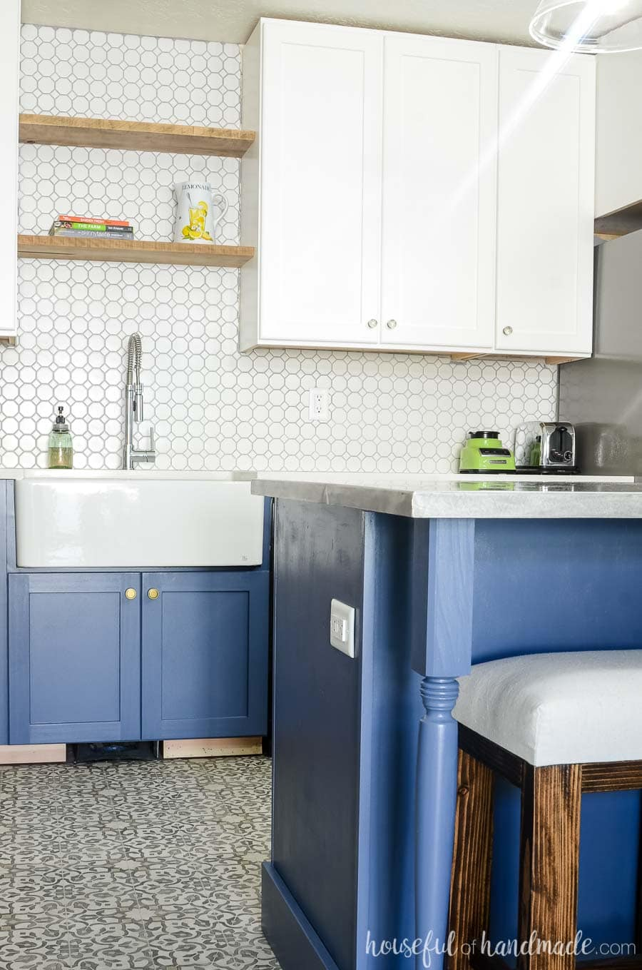 Gorgeous white and gray navy kitchen with textured white porcelain tile. Rustic floating shelves and a farmhouse sink are perfect for a budget farmhouse kitchen remodel. Housefulofhandmade.com