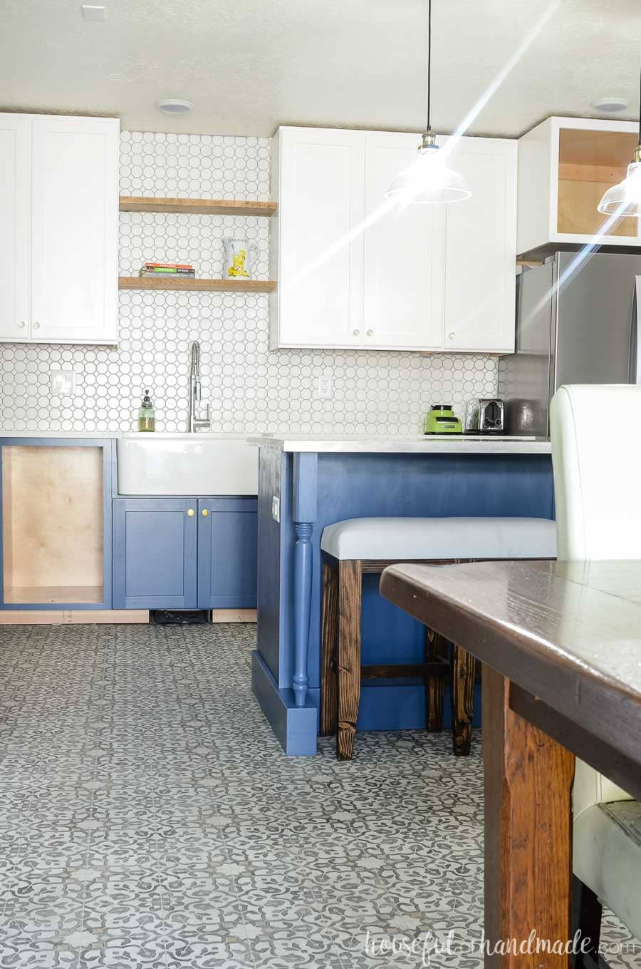 Stunning white and navy farmhouse kitchen. The kitchen island looks like a piece of furniture in the center of the kitchen and the open shelves above the farmhouse sink keep the space bright and open. Housefulofhandmade.com