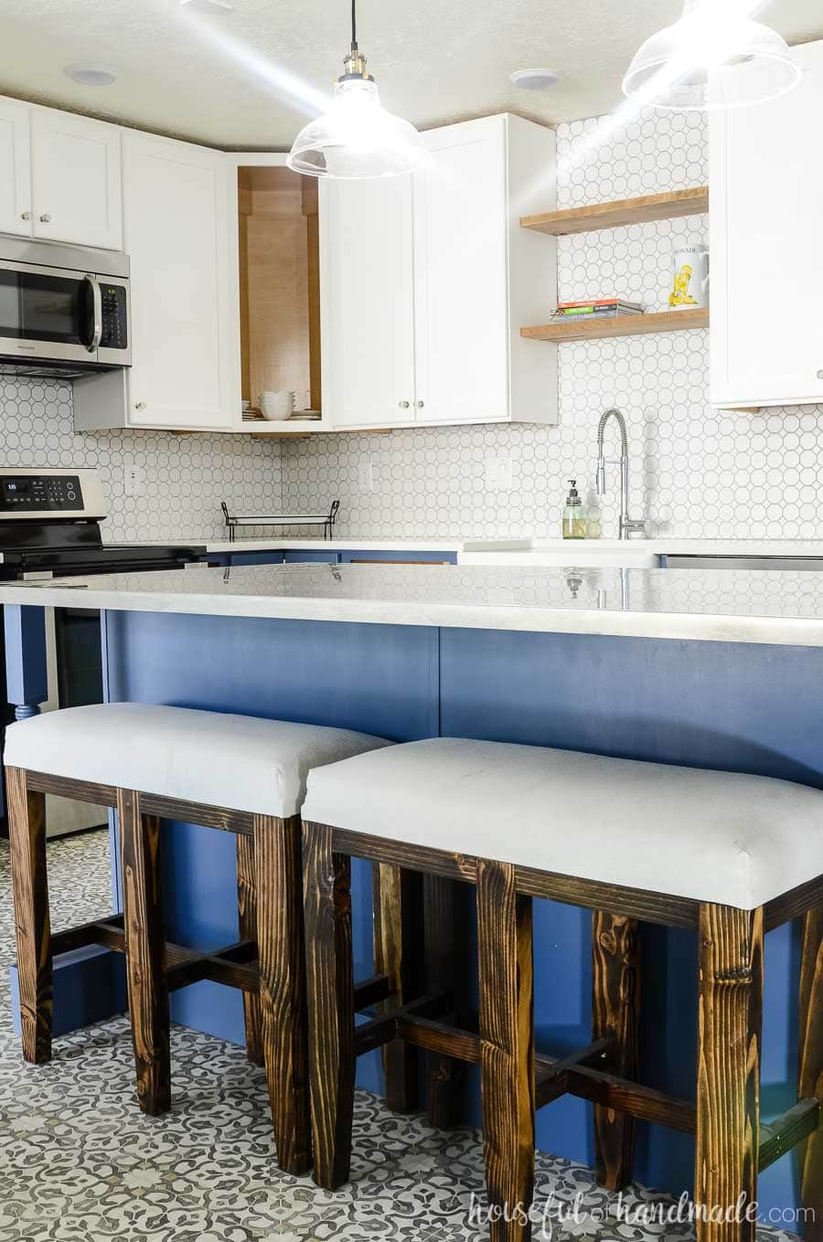 Navy blue kitchen island with rustic bar stool benches are the perfect centerpiece for this budget farmhouse kitchen remodel. Housefulofhandmade.com