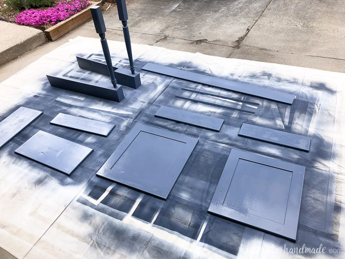 Wood pieces for kitchen island shown outside on tarp being painted with paint sprayer.