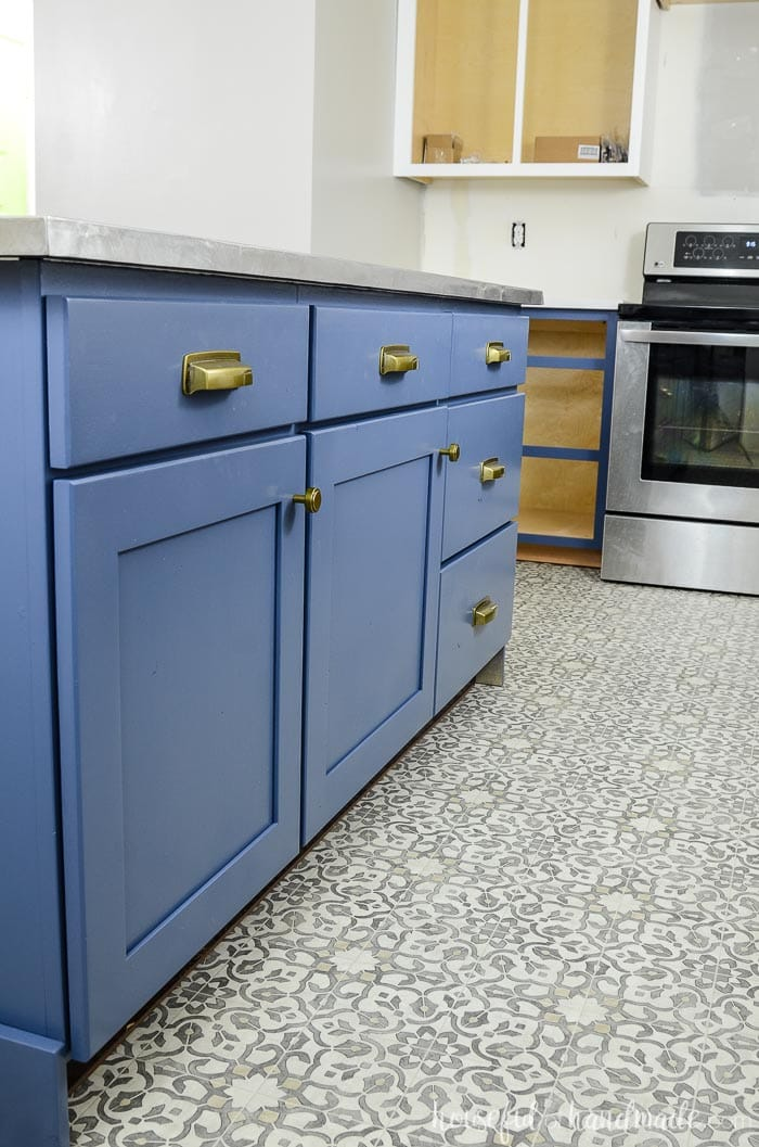 Brass hardware on a soft navy kitchen island.