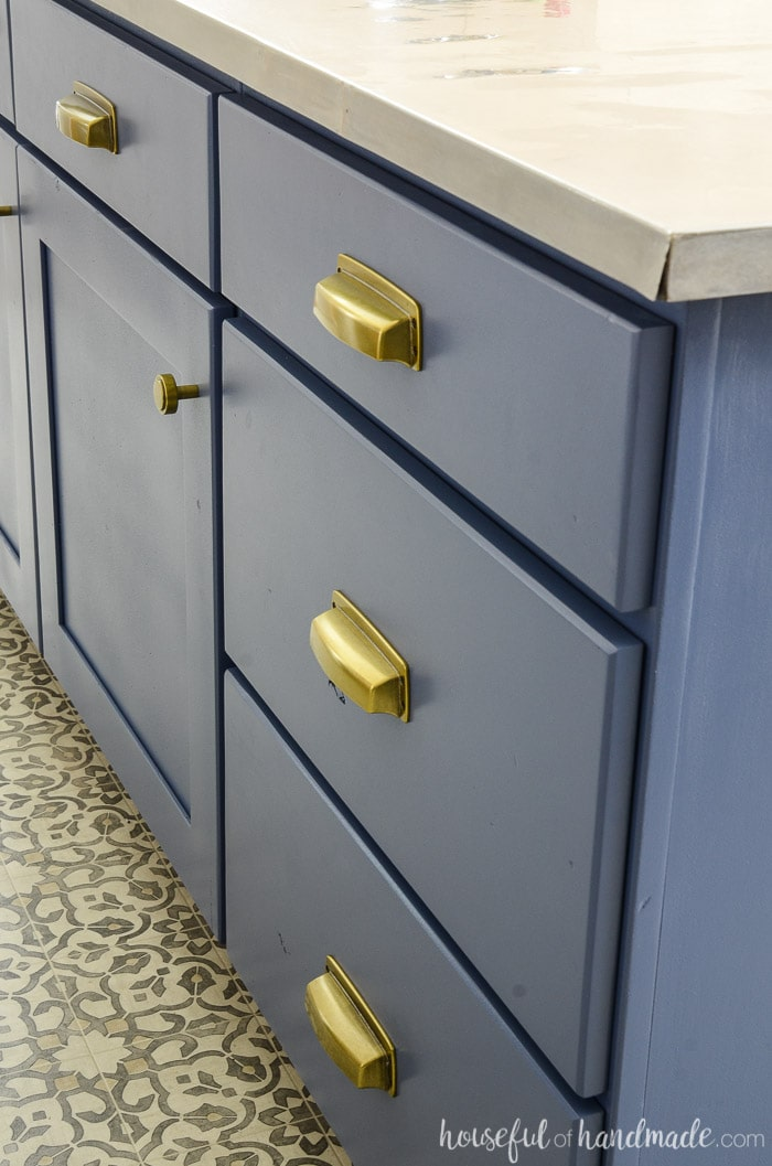 Close up of Brass cup pulls on this navy kitchen island makeover.