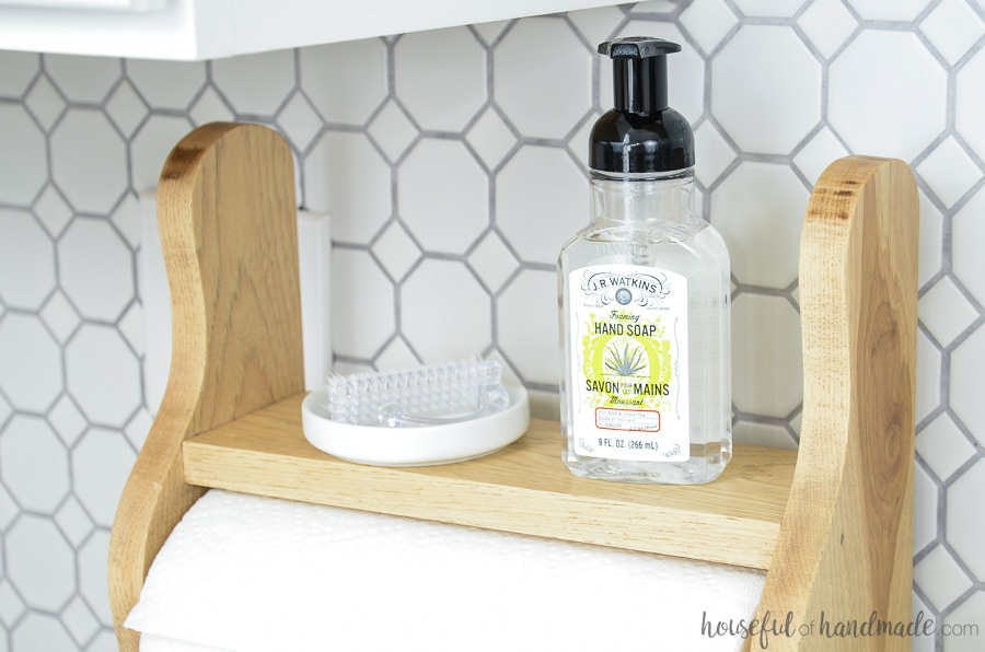 Love this farmhouse paper towel holder with shelf. Its the perfect place to store hand soap and a nail scrubber to keep clutter off the countertops. Housefulofhandmade.com