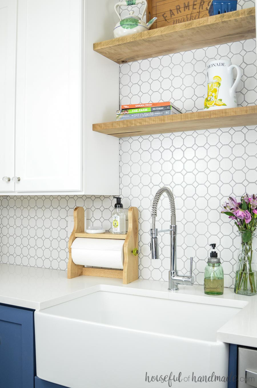 White kitchen with open shelves and white octagon tile backsplash. Beautiful farmhouse paper towel holder with shelf behind apron front sink. Housefulofhandmade.com