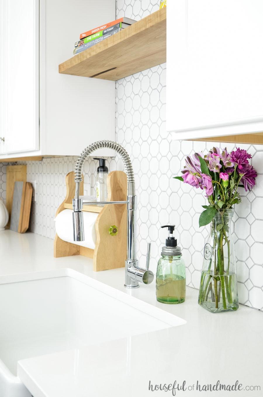 Beautiful apron front sink with white quartz countertops. Decorated with purple flowers, mason jar soap dispenser, wood farmhouse paper towel holder and white tile backsplash. Housefulofhandmade.com