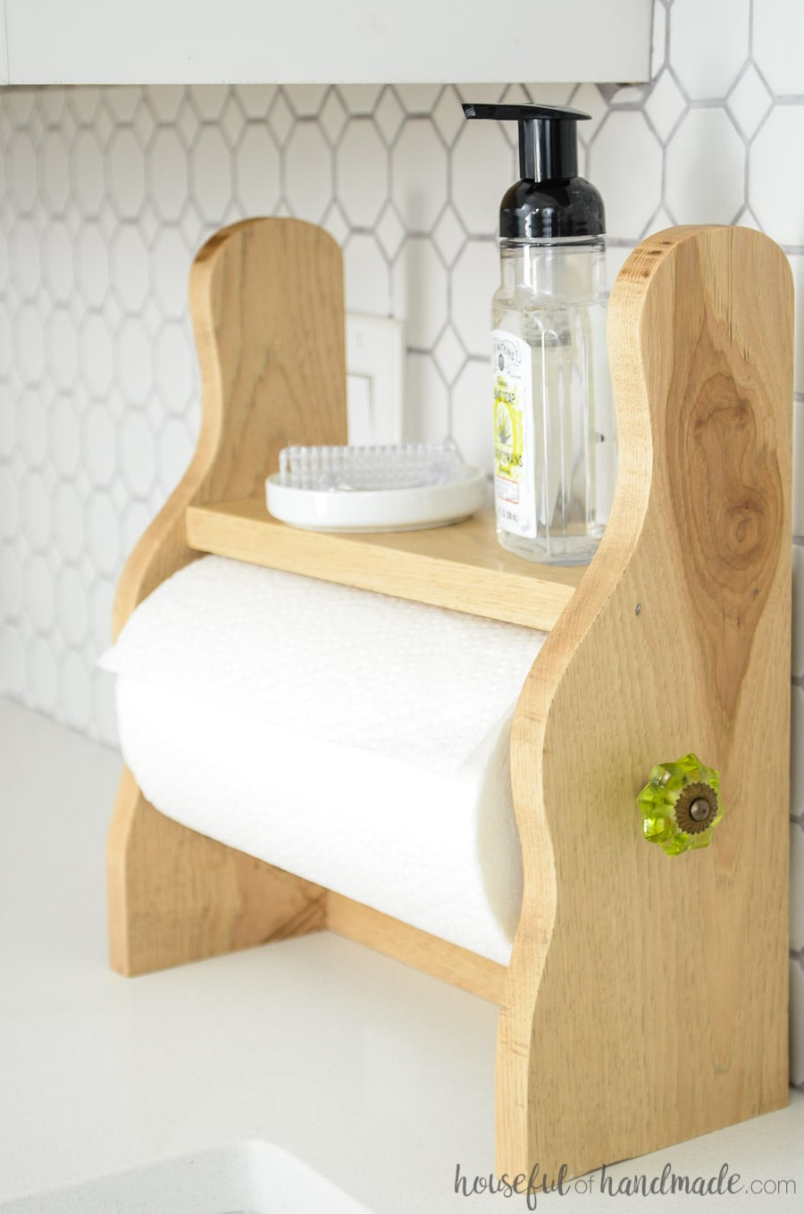 Make this farmhouse paper towel holder in just 15 minutes with this easy tutorial. The cute sides are cut with a jig saw and the little shelf keeps your kitchen clean. Housefulofhandmade.com