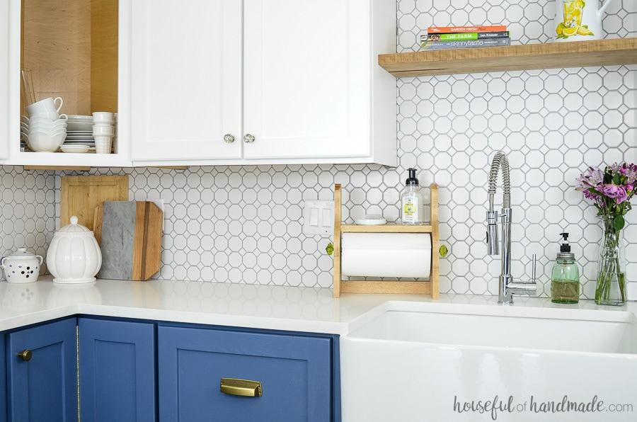 This beautiful farmhouse paper towel holder is a fun and easy craft to make in just 15 minutes. See how it looks in our farmhouse kitchen with white cabinets and white tile backsplash with blue base cabinets. Housefulofhandmade.com