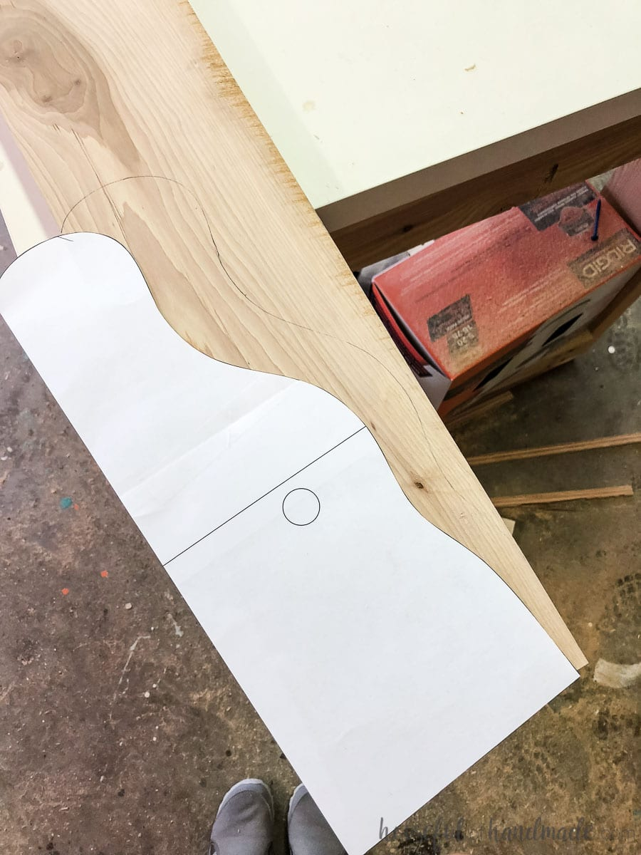 Printed template being traced onto the 1x6 board to create a farmhouse paper towel holder.