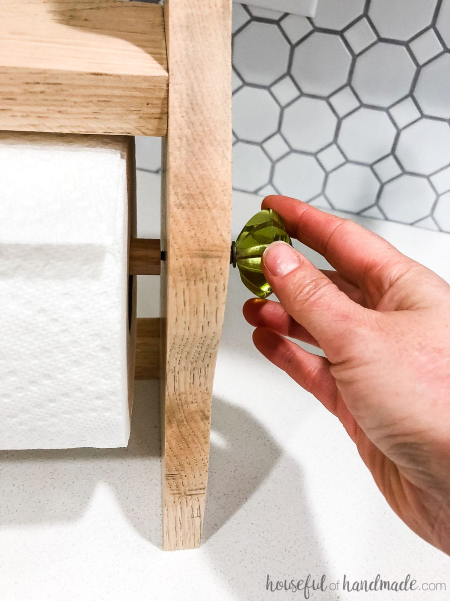 Wood paper towel holder shown with decorative knobs being secured to the side