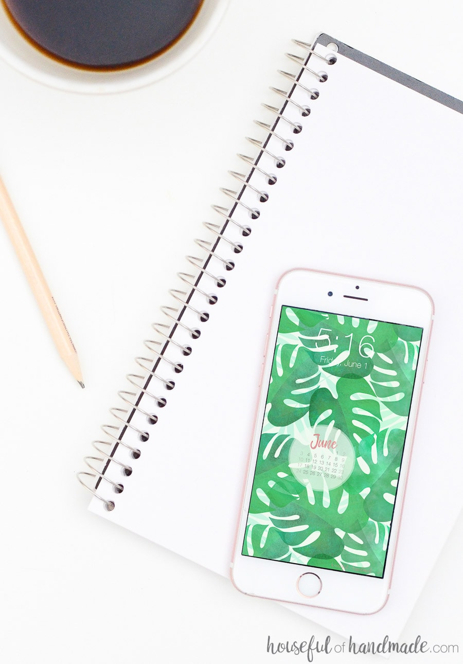 iPhone on a notebook displaying watercolor leaf digital background and calendar.
