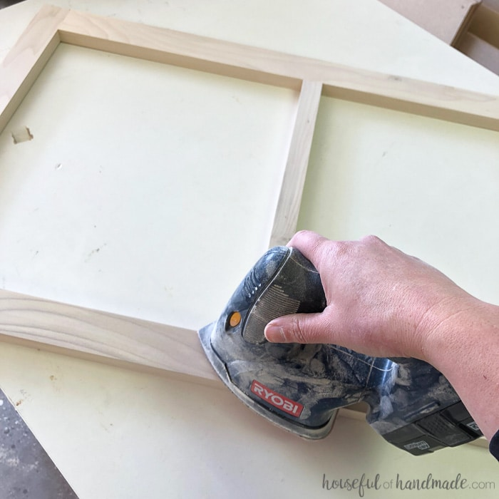 Sand the wood with 220 grit sandpaper to get super smooth. Learn all the tips for how to paint unfinished cabinets at Housefulofhandmade.com.