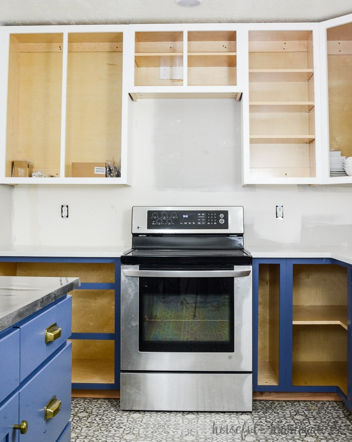 White painted upper cabinets with soft navy base cabinets missing their doors. See how to paint unfinished cabinets at Housefulofhandmade.com.