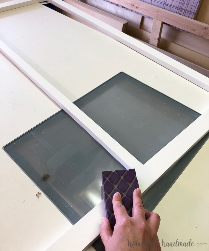Lightly sanding between coats give your painted cabinets a super professional paint finish. Learn how to paint unfinished cabinets at Housefulofhandmade.com.