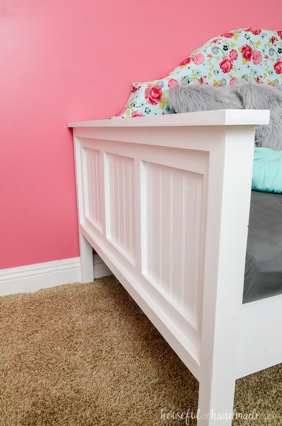 Beadboard details make the sides of this upholstered day bed so chic. Bright white frame with a bold floral upholstered headboard make this day bed the perfect focal point of the room. Free build plans at Housefulofhandmade.com.