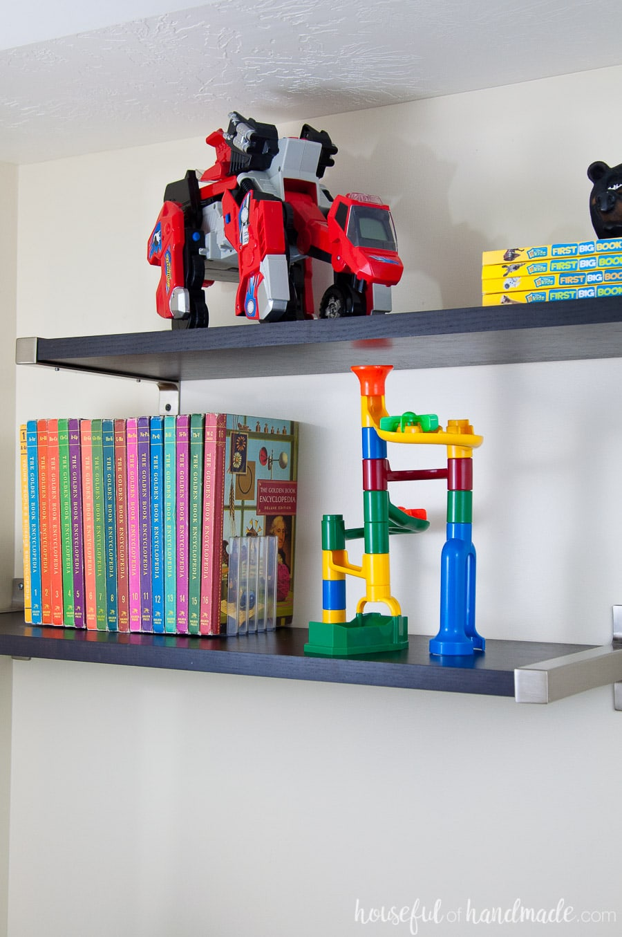 Floating wall shelves from Ikea to store books and toys in a boys bedroom.