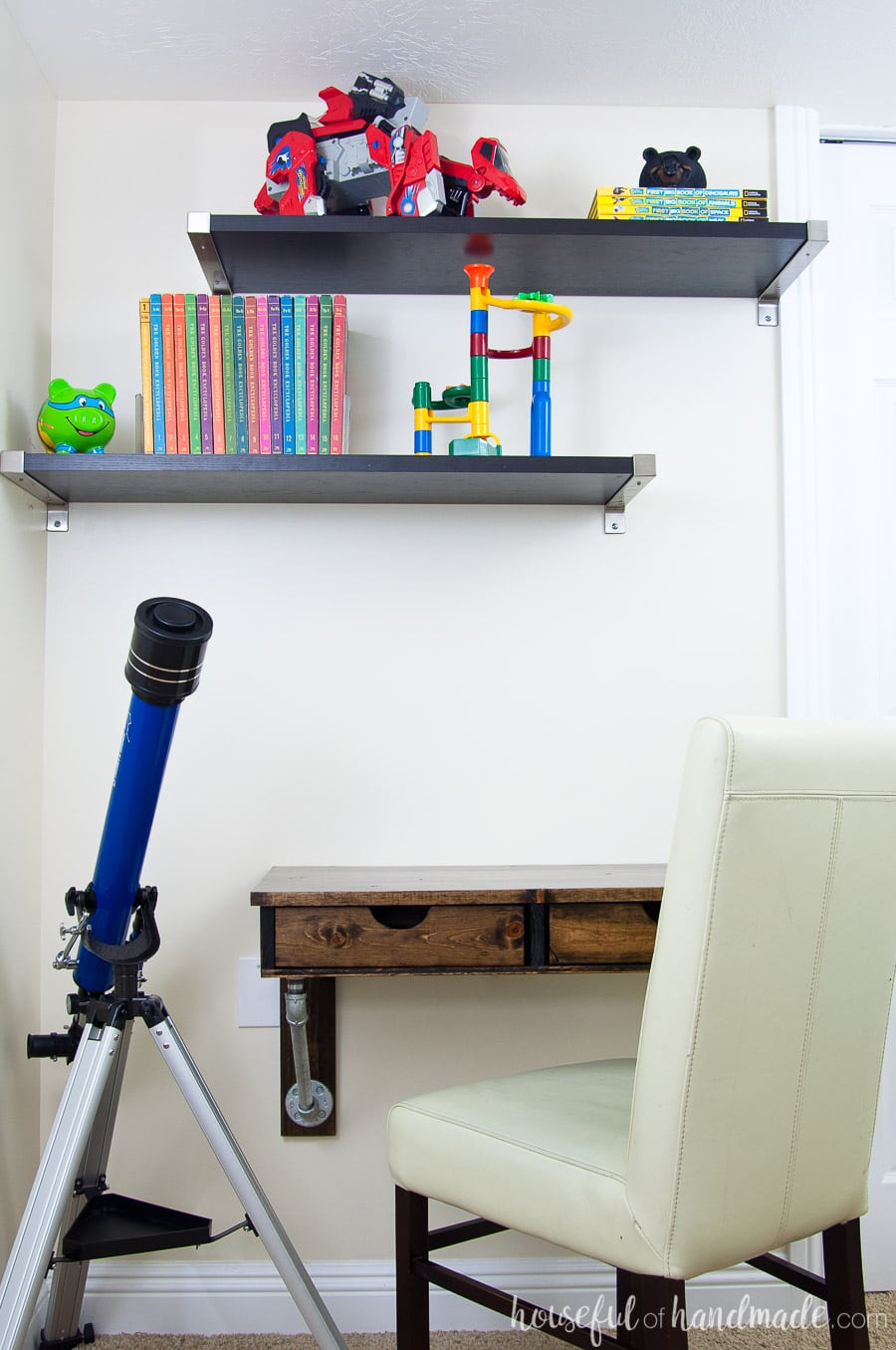 Wall mounted rustic desk in a boys bedroom. Shelves above hold encyclopedias and toys. Telescope sitting next to the desk.
