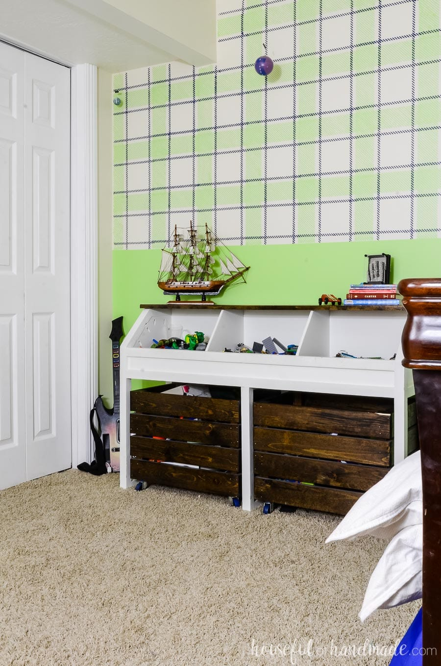 White and dark wood toy storage unit with open bins on the top and large rolling bins underneath. In a boys bedroom with a green plaid painted wall and neutral beige carpet.