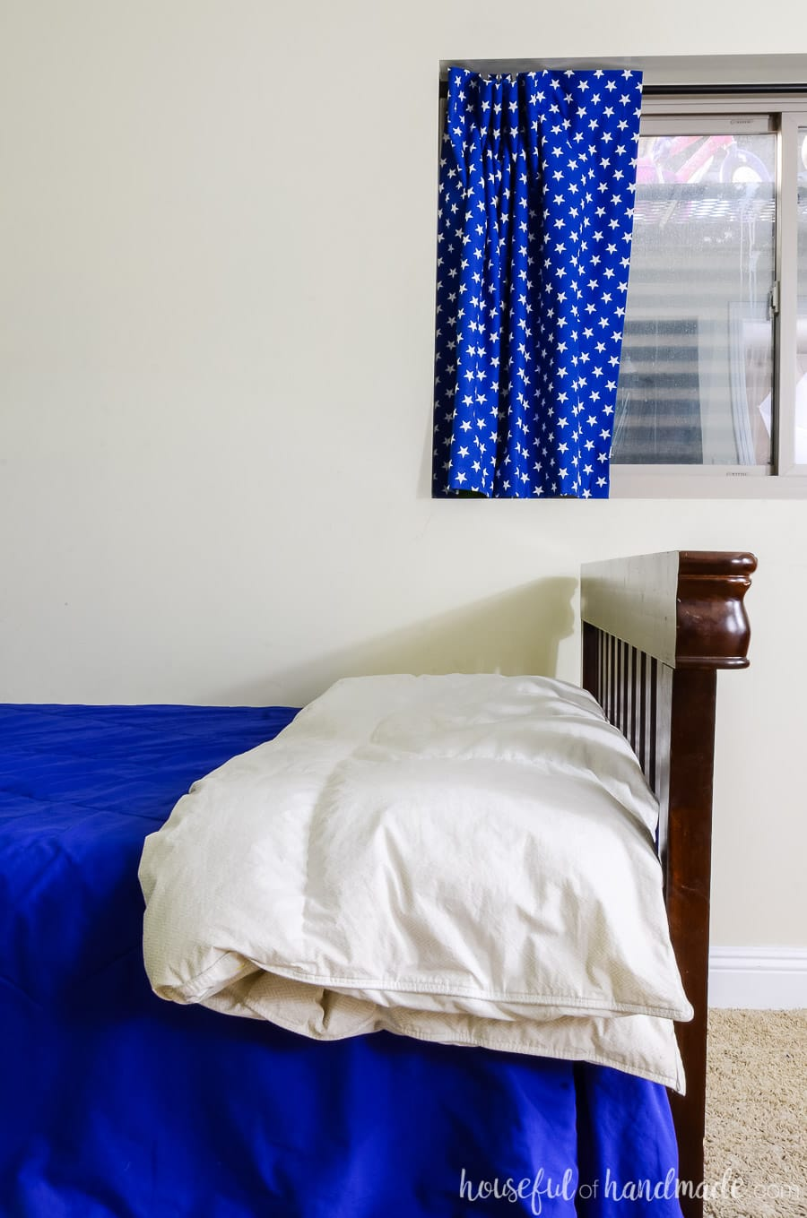 The foot of the bed with a dark wood craftsman footboard and white down comforter. Black out curtains in the window with blue fabric with white stars on it.