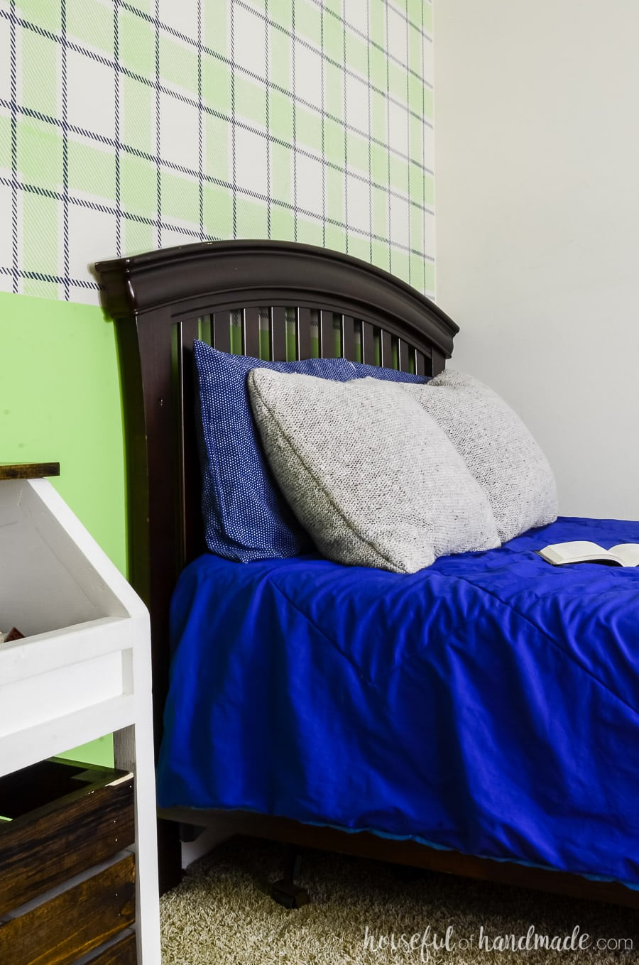 Dark wood craftsman headboard in a boys bedroom. Blue bedding with a green plaid wall design on the back wall.