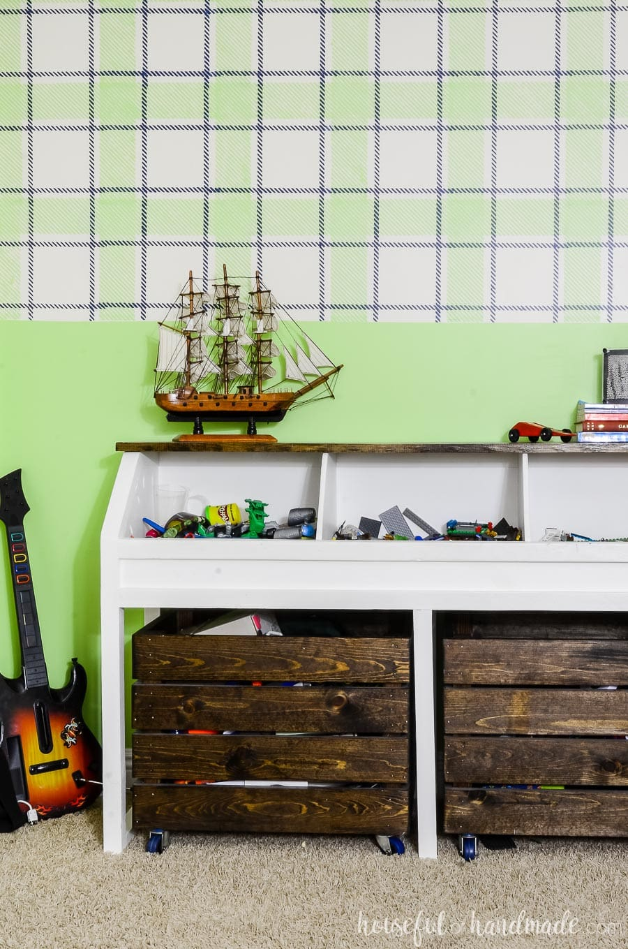 Rustic toy storage console full of Legos and action figures. In front of a statement wall painted with with a green & navy plaid design on top and green solid on the bottom. Wii guitar in the corner.
