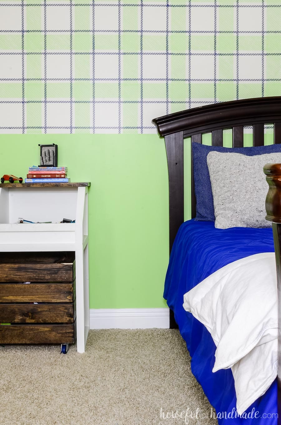 Boys bedroom with blue & green plaid wall design. Rustic toy storage console and arched headboard bed frame in front of wall.