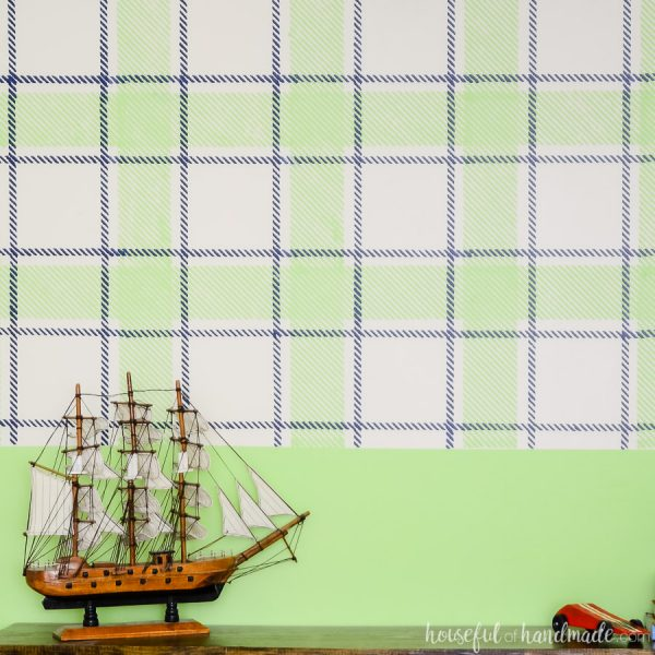 Toy pirate ship on top of the toy console in front of a navy & green plaid wall design.