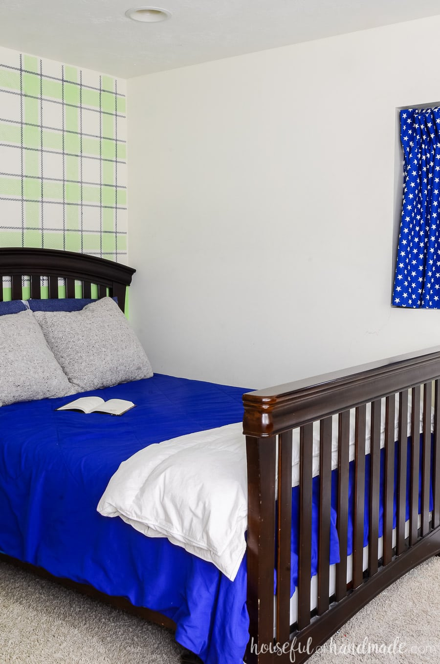 Dark wood bed with blue comforter and knit pillows. Focal wall behind bed is painted blue & green plaid with a wall stencil.