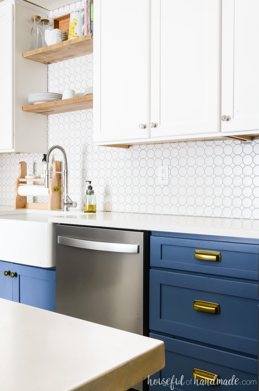 Navy base cabinets with white quartz counter top and white upper cabinets.