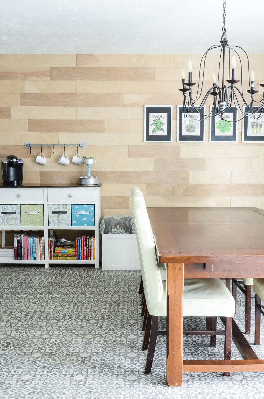 Dining room with black chandelier and wood accent wall. Large rustic table and white coffee station.
