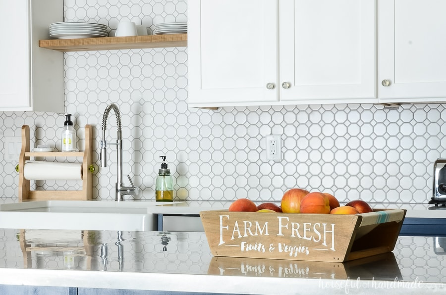 Farmhouse fruit bowl on kitchen island in front of white kitchen cabinets with white porcelain backspace.