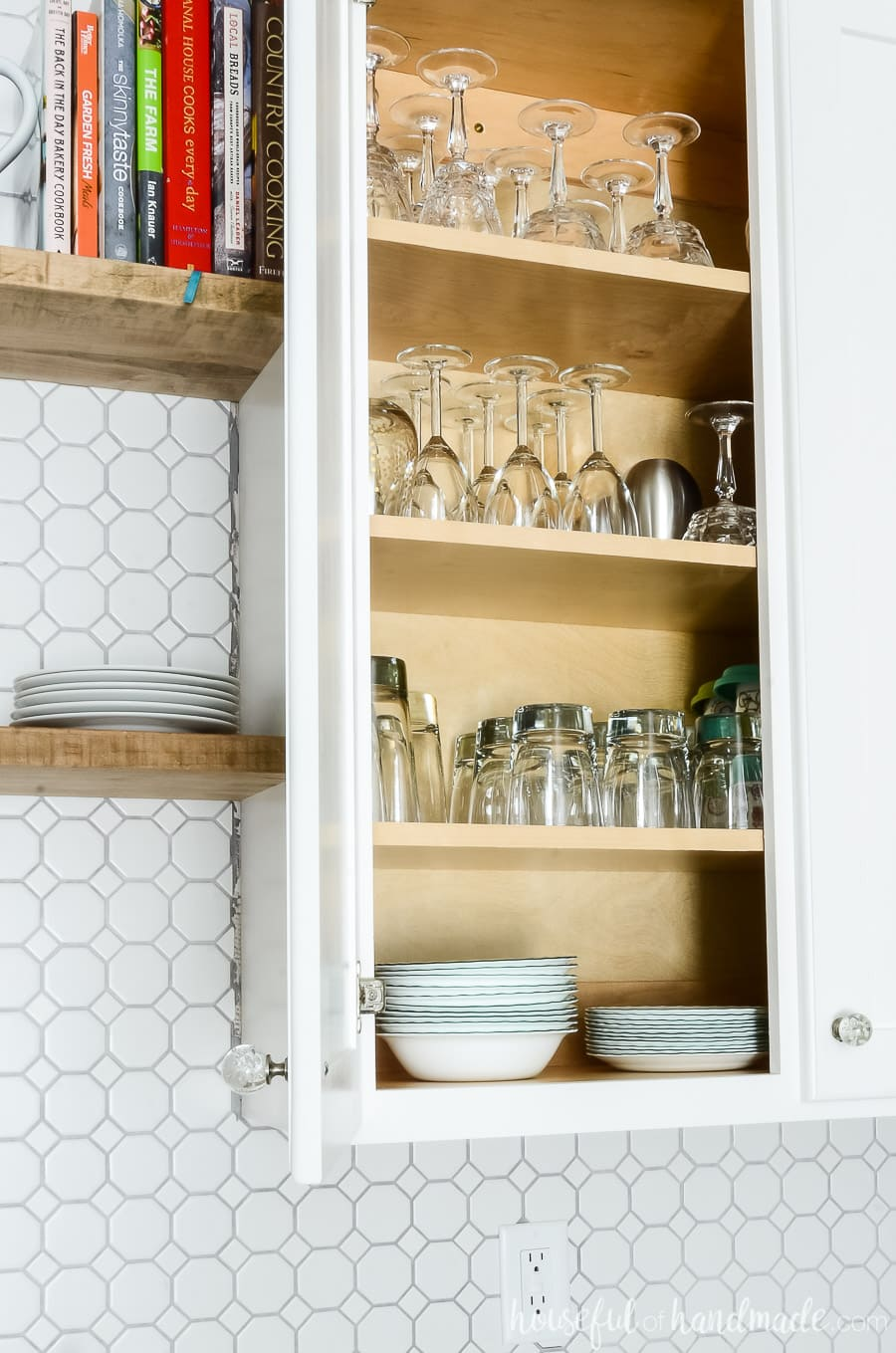 """White 42"""" upper cabinet with goblets, wine glasses, cups and bowls inside with one door open showing the concealed hinges on the inside of the cabinet door."""