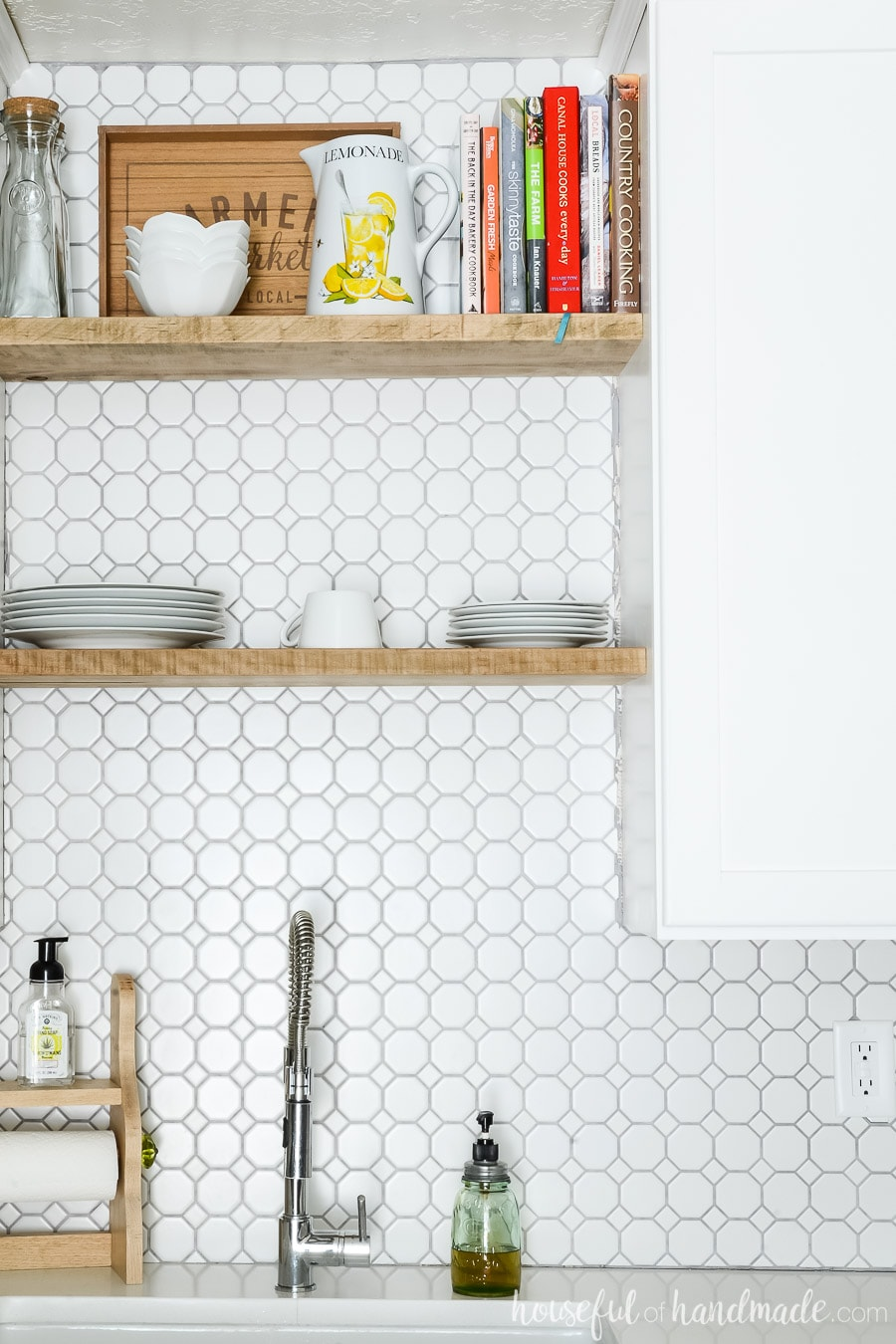 Close-up of chunky open shelving about kitchen sink. Retro octagon white backsplash tile with gray grout.