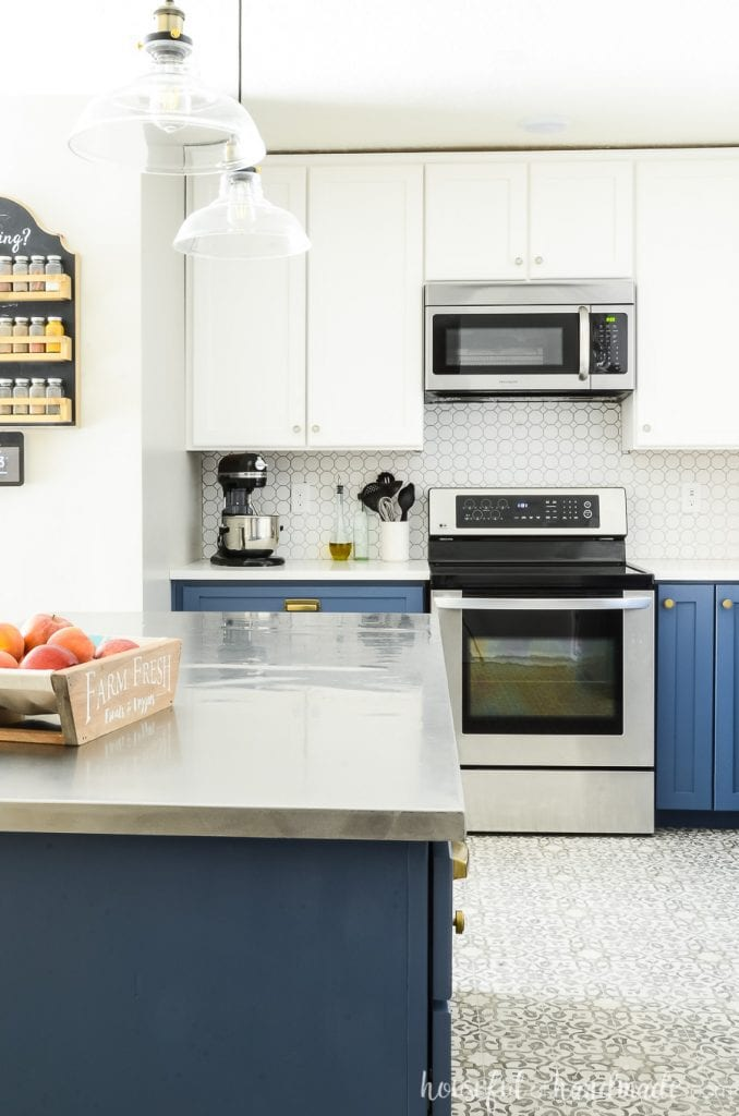 Two tone kitchen with Durango Blue lower cabinets and white upper cabinets. White octagon porcelain tile backspace and silver appliances.