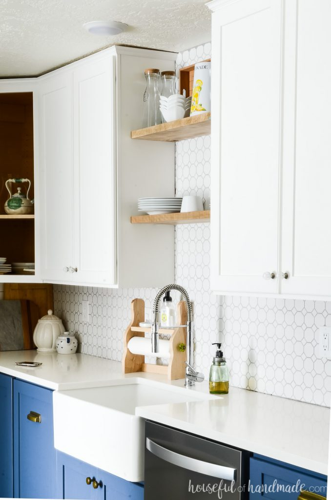 Close up of the white wall cabinets in the two tone kitchen. Farmhouse sink with open shelving above it.