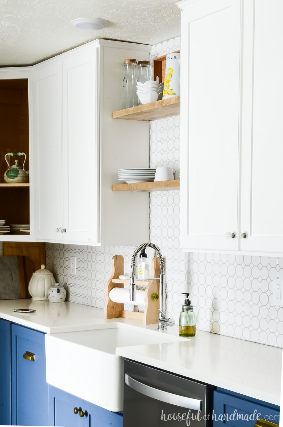 Close up of the white upper cabinets in the two tone kitchen. Farmhouse sink with open shelving above it.