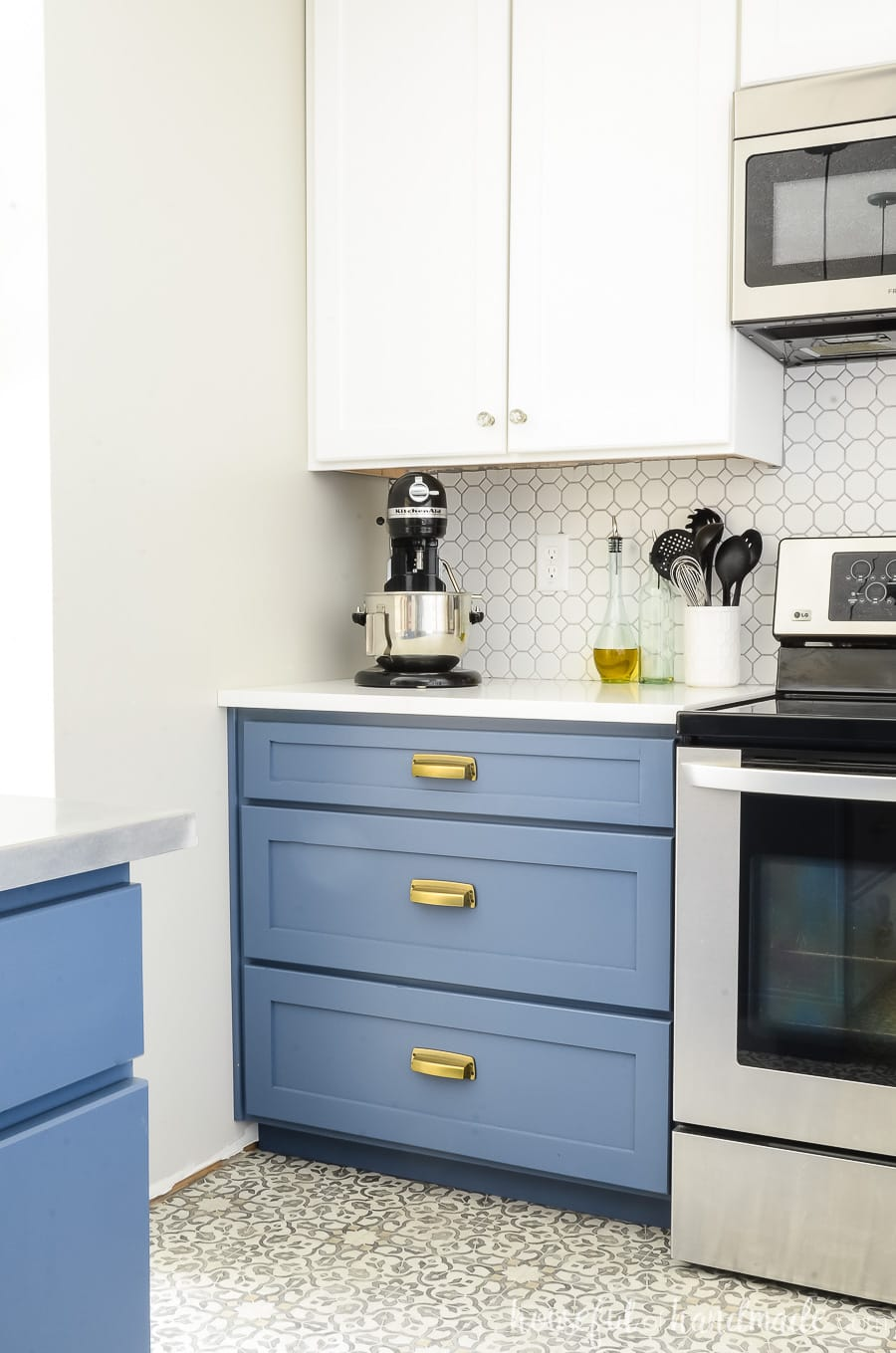 Blue painted lower cabinets with large base cabinet drawers next to the strove. White upper cabinets make this a two tone kitchen.