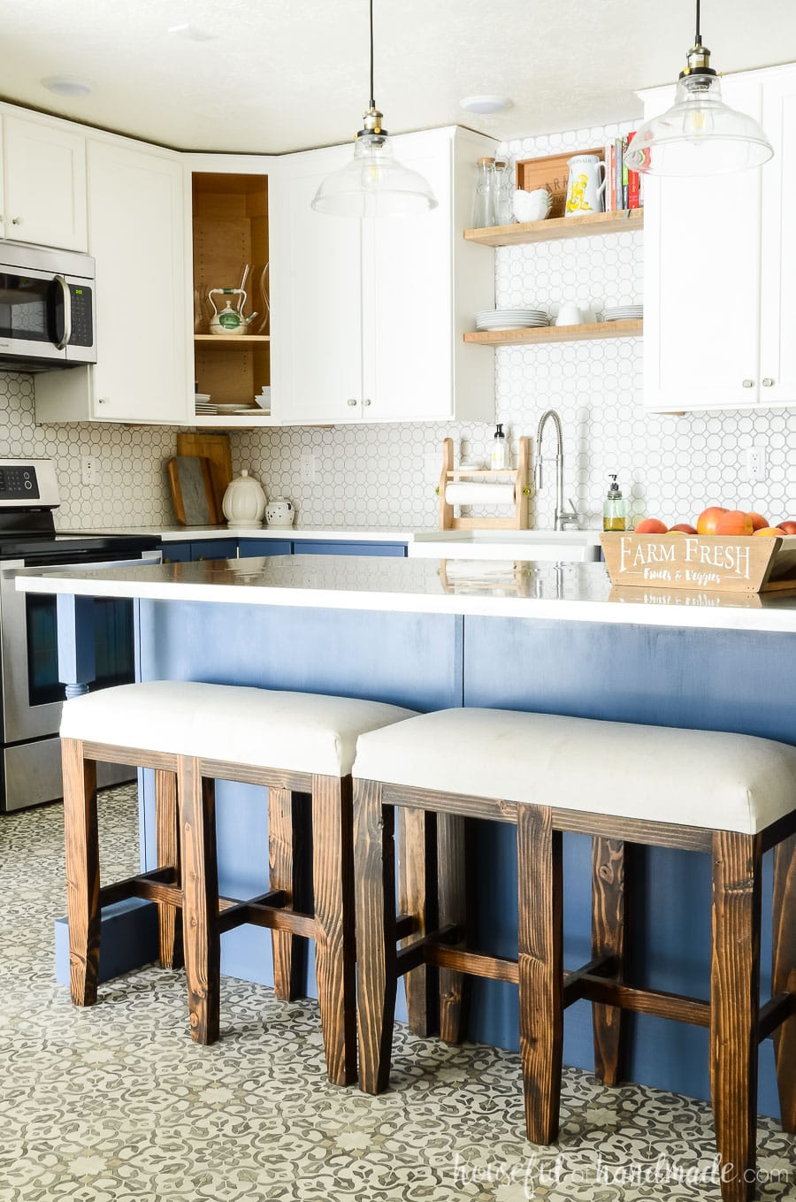 Blue farmhouse kitchen island with bar stool benches at it. White two tone kitchen cabinets in the background.