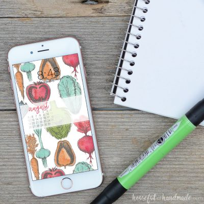 Digital background with August calendar. Free digital wallpaper of colorful hand-drawn vegetables on a smartphone screen next to sketchbook.
