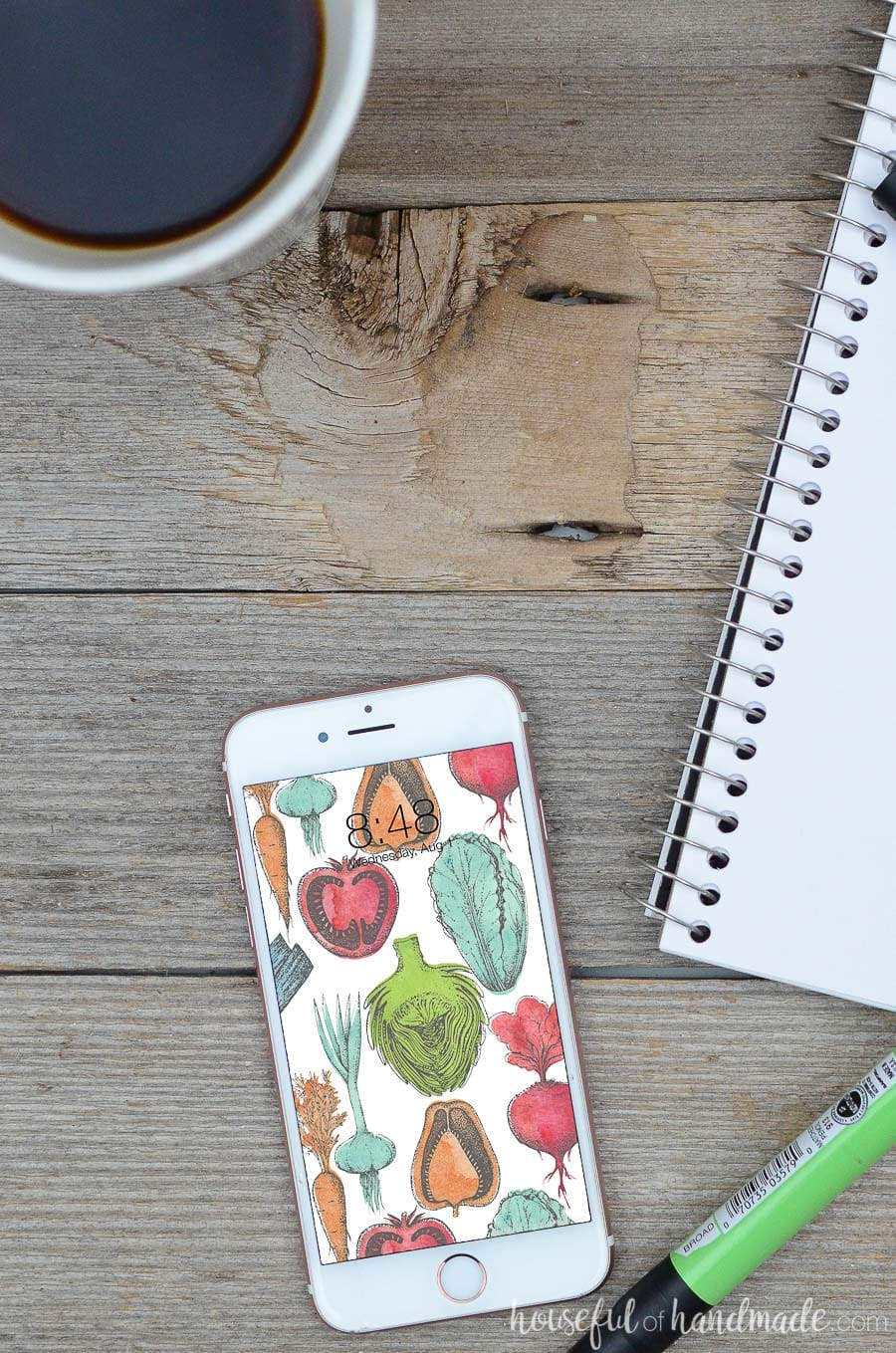 White iPhone smartphone with colorful vegetable design digital wallpaper on it. Phone is laying on a wood background with sketchbook and cup of coffee next to it.
