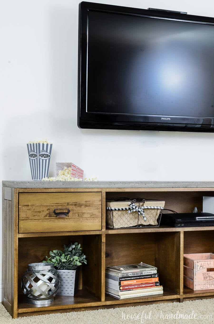 Televison mounted on the wall above a warm brown rustic TV stand with concrete top. Showing open shelving with books and decor items inside.