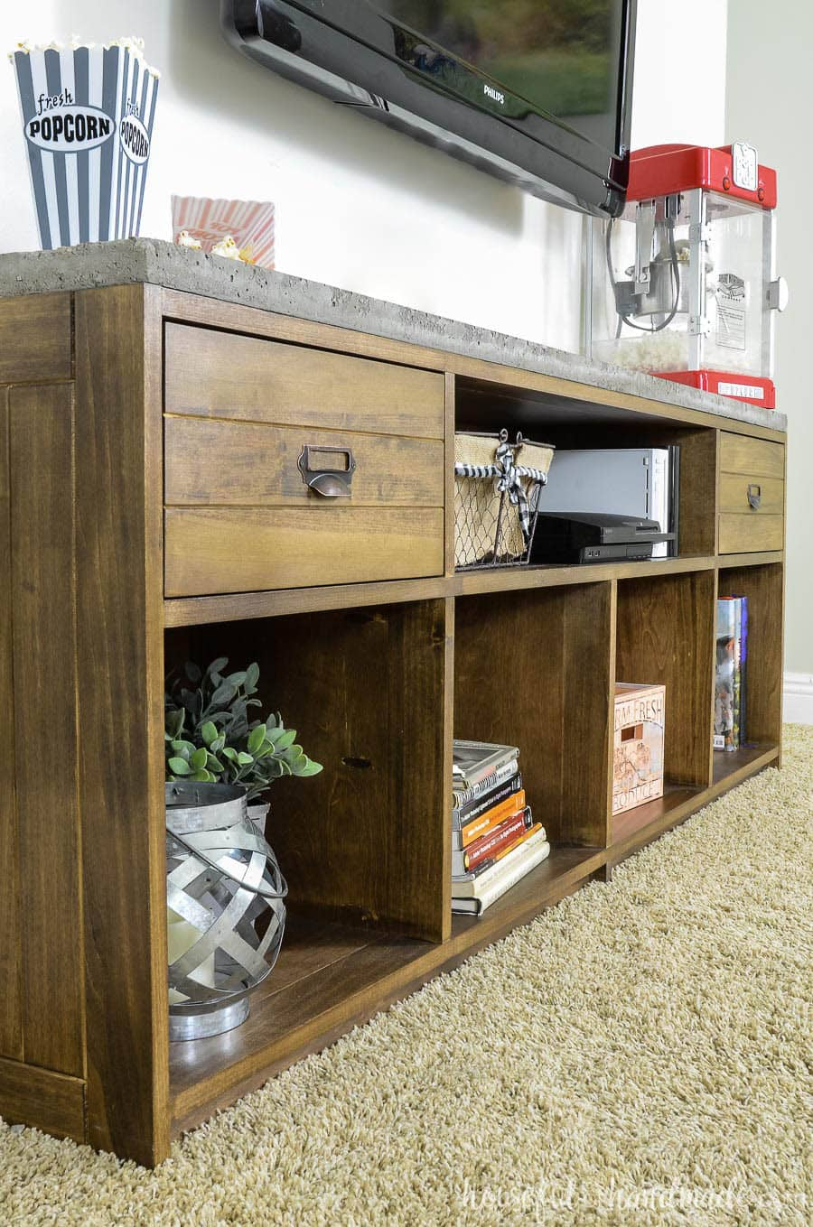 Angled view of medium brown stained TV stand with 2 drawers and a concrete top.