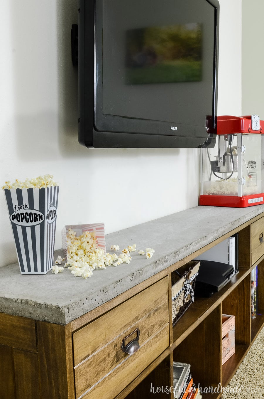 Close up of the concrete top on the rustic TV stand. Styled with popcorn popper and popcorn containers.