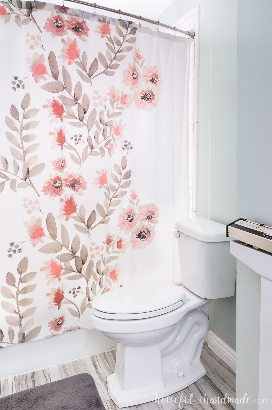 White shower curtain with coral flowers and brown leaves competes the spa-like master bathroom retreat.