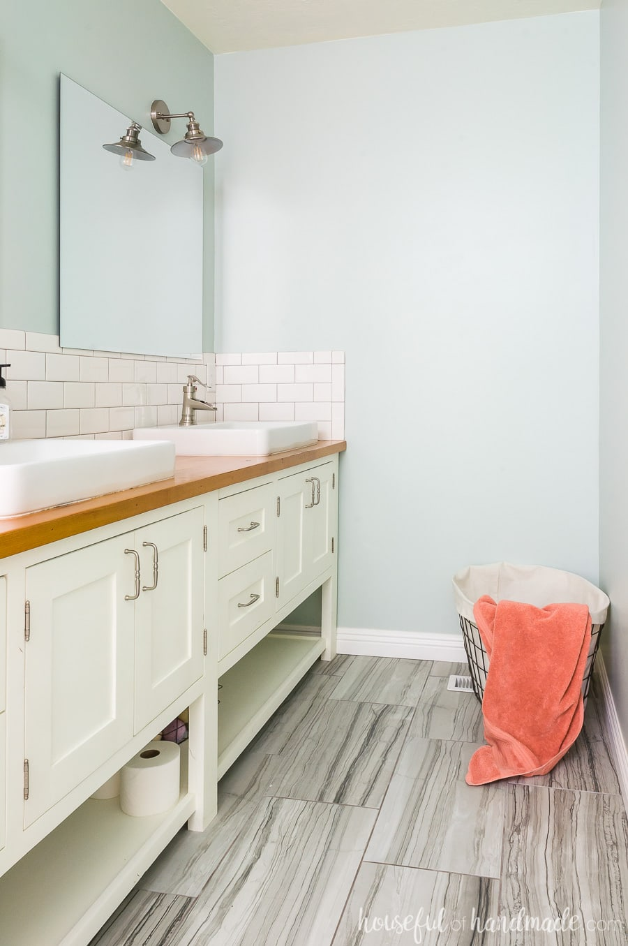 Create a beautiful master bathroom retreat with soft green walls, white vanity, real wood vanity top, and vessel sinks.