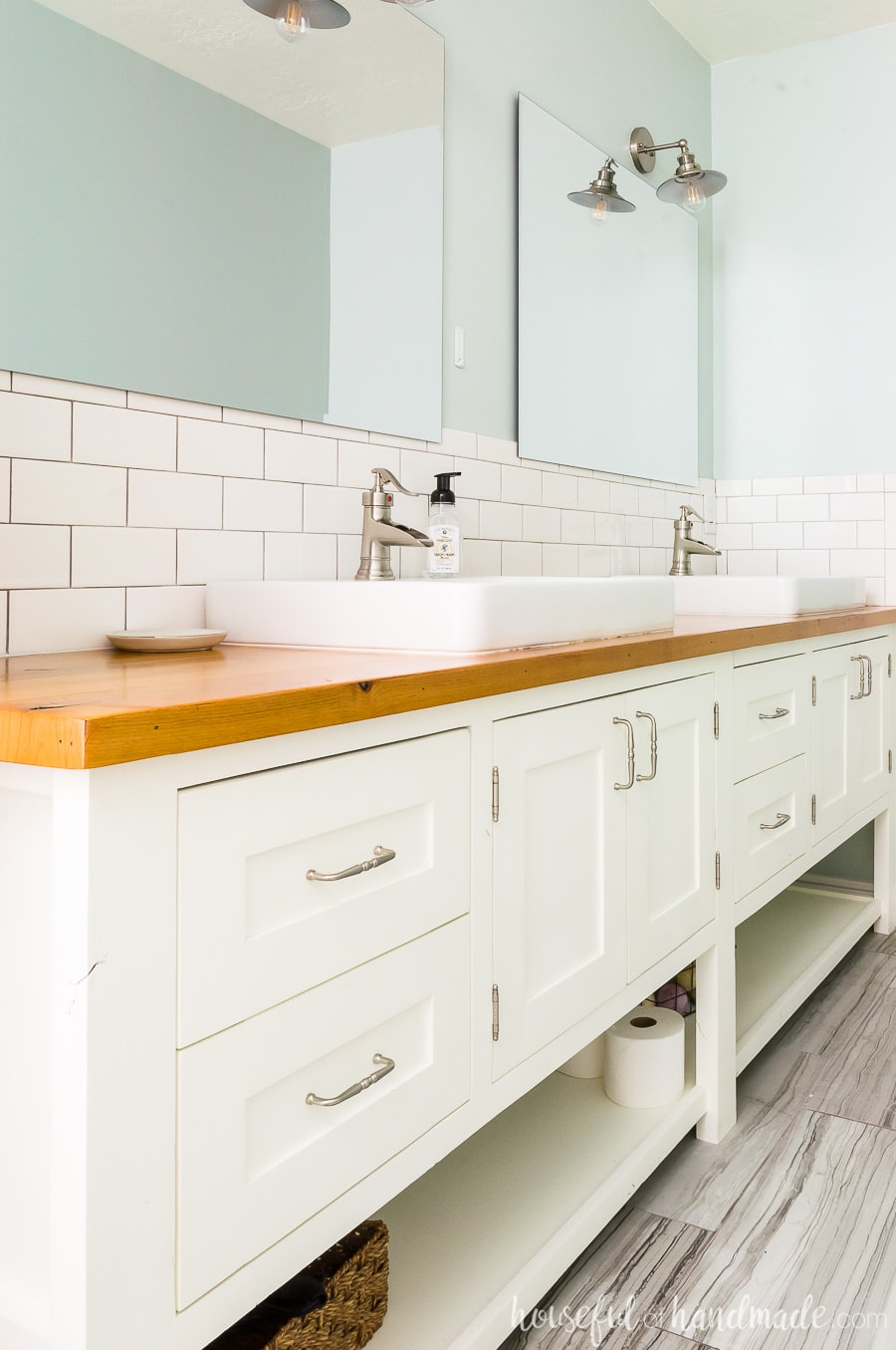 A DIY master bathroom retreat with a large 8' white mission style open shelf bathroom vanity with natural wood vanity top. White square vessel sinks and white subway tile on backsplash. Frameless mirrors against gray-green walls make a peaceful space.