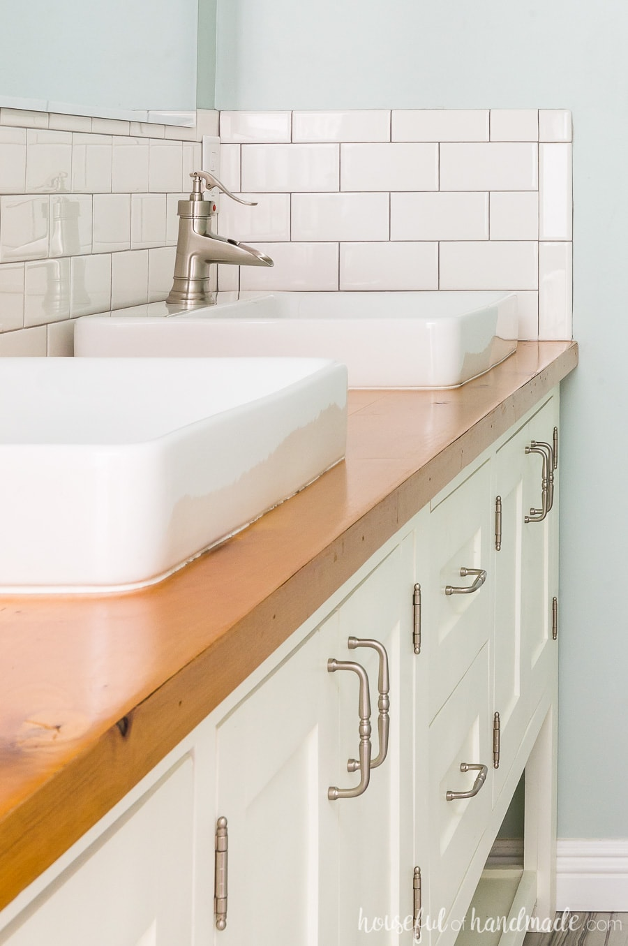 Two large vessel sinks on top of a natural wood vanity top make this a master bathroom retreat. The white subway tile backsplash and white vanity is the perfect balance.